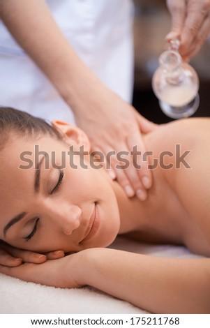Beautiful woman having a wellness back massage. pretty woman laying on massage table and getting oil massage - stock photo