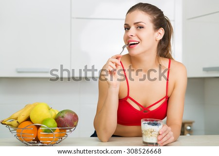 Beautiful woman having an oatmeal with berries for breakfast