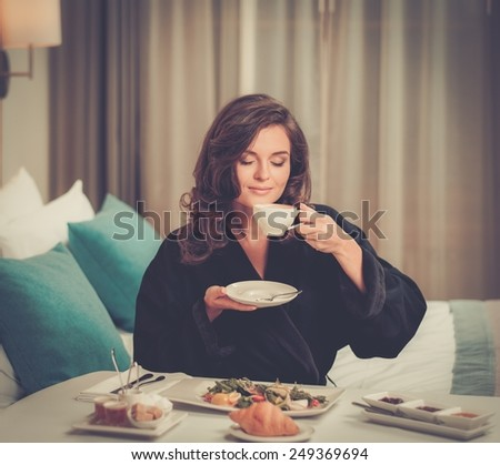 Beautiful woman having breakfast in a hotel room - stock photo
