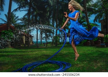 Beautiful woman having fun with garden hose splashing summer rain. - stock photo