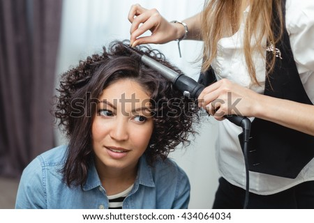 Beautiful woman having her hair curled in barber salon
