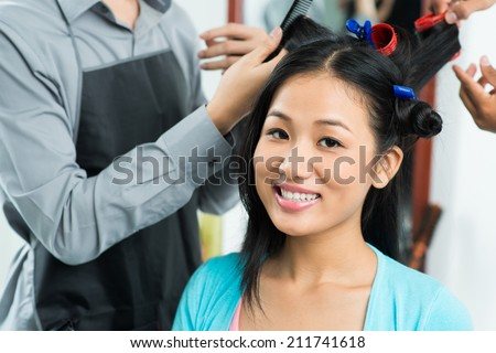 Beautiful woman having her hair curled in salon - stock photo