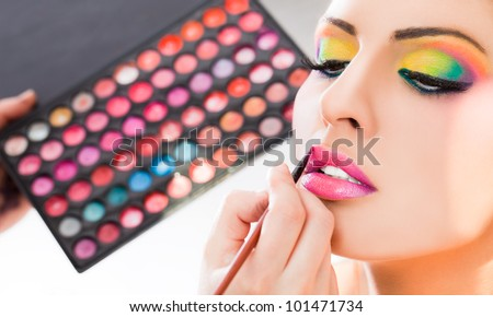 Beautiful woman having lipstick applied by make-up artist - stock photo