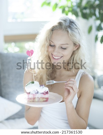 Beautiful woman having raspberry cake with fork in house - stock photo