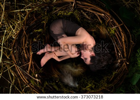 Beautiful woman hiding alone in an empty bird's nest - stock photo