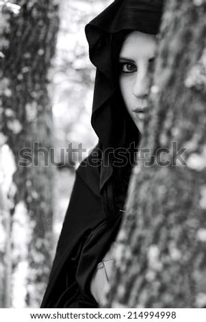 Beautiful woman hiding behind tree - stock photo