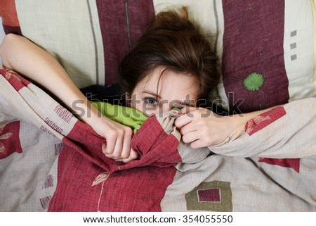 Beautiful woman hiding face under cover lying in bed. Female sparky eyes looking in camera closeup. Sweet dreams, flirtation, playing game, wake up - stock photo