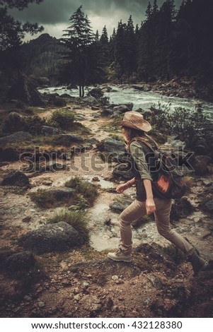 Beautiful woman hiker jumping on the stones near wild mountain river. - stock photo