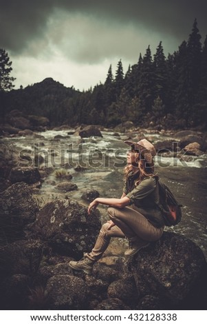 Beautiful woman hiker sitting on the stone near wild mountain river. - stock photo