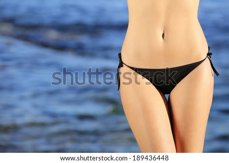 Beautiful woman hips with a bikini on the beach with the sea in the background           - stock photo