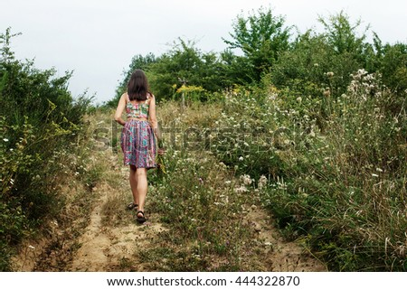 beautiful woman hipster walking and holding rustic bouquet in grass meadow, summer travel, space for text