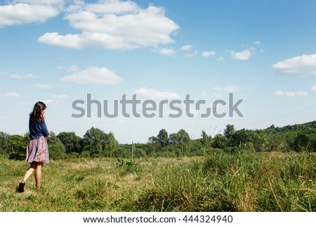 beautiful woman hipster walking at green summer field on background of blue sky, space for text