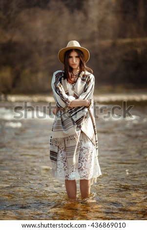 beautiful woman hipster wearing hat and poncho standing in water of river, stylish outfit, boho travel concept