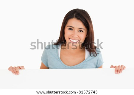 Beautiful woman holding a  board while standing against a white background - stock photo