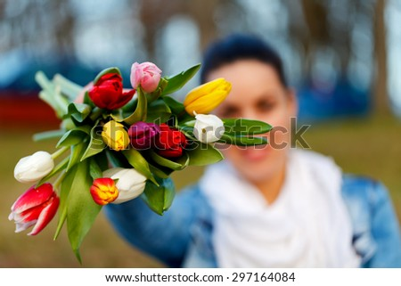 Beautiful woman holding a bouquet in her hands - stock photo