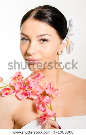 Beautiful woman holding a branch of orchid flowers - stock photo