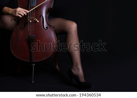 Beautiful woman holding a cello with selective light in black dress - stock photo