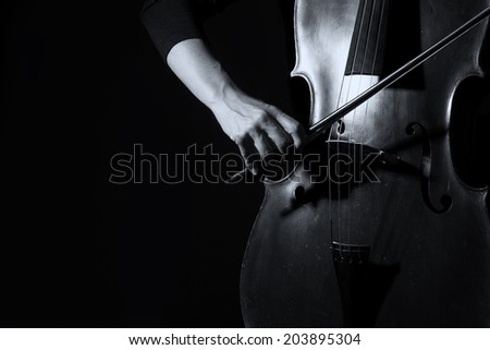 Beautiful woman holding a cello with selective light in black dress artistic conversion - stock photo