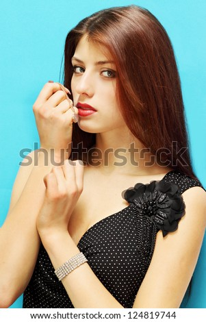 beautiful woman holding a gold medallion in the shape of heart - stock photo