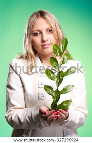 Beautiful woman holding a green plant studio shot - stock photo