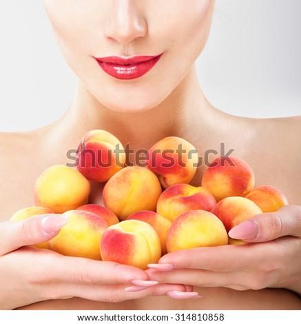 Beautiful woman holding a juicy apricots. Perfect skin. Professional makeup. - stock photo