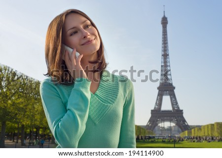 Beautiful woman holding a phone with Eiffel Tower in background - stock photo