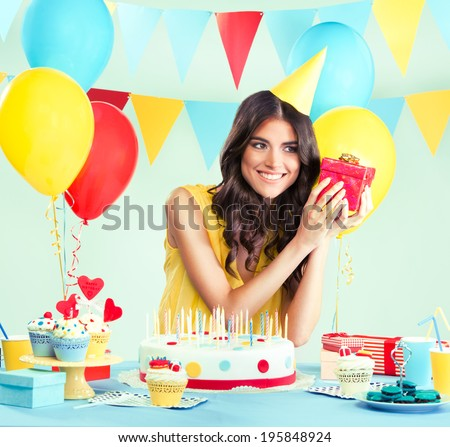 Beautiful woman holding a present at her birthday party - stock photo