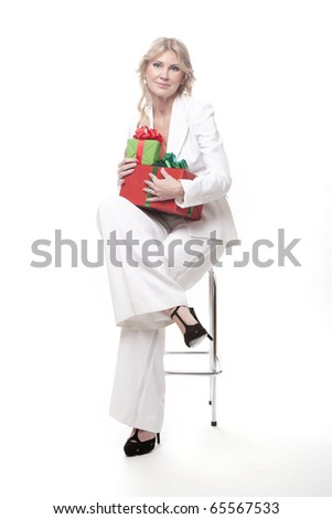 Beautiful woman holding a present in a gnomes hat, isolated on white