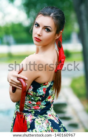 beautiful woman holding a red umbrella in the city street