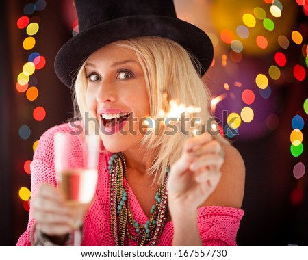 Beautiful woman holding a sparkler and a glass of champagne while having fun on a New Year's Eve. - stock photo