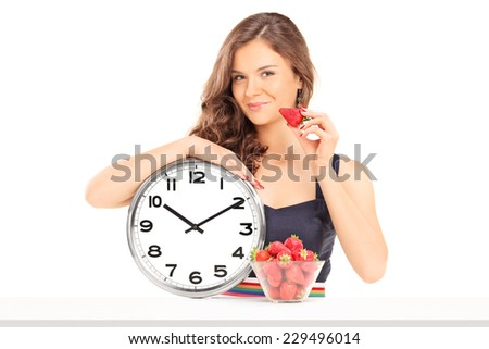 Beautiful woman holding a strawberry and a clock isolated on white background - stock photo