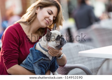 Beautiful woman holding adorable fawn french bulldog in her lap in cafeteria. Selective focus on dog.