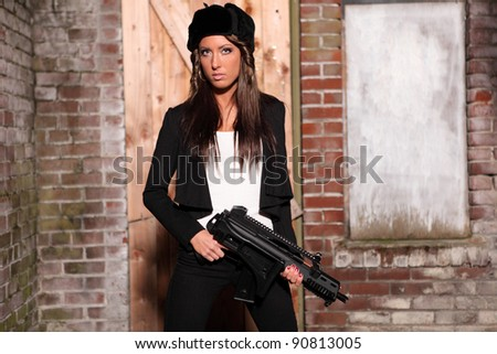 Beautiful woman holding an automatic rifle.
