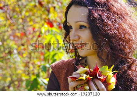 beautiful woman holding autumn leaves