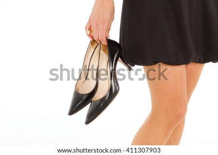 Beautiful woman holding black shoes in the hand