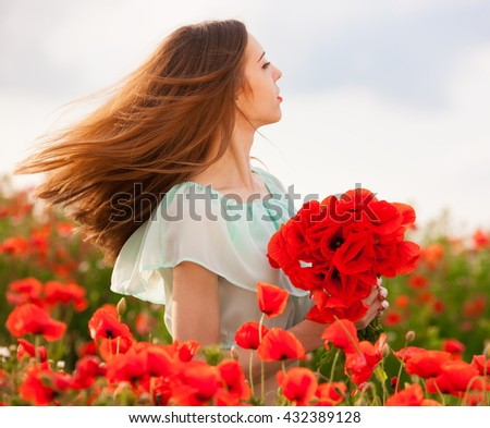 Beautiful woman holding bouquet red flowers poppies. Has romantic face, long hair, sexy lips, clothed blouse. Has slim body. Portrait in nature field. Sunny day. Close up.