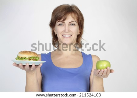 beautiful woman holding burger and green apple
