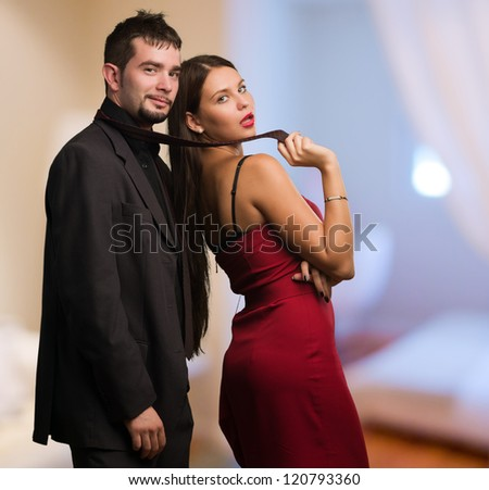 Beautiful Woman Holding Businessman Tie at a bedroom - stock photo