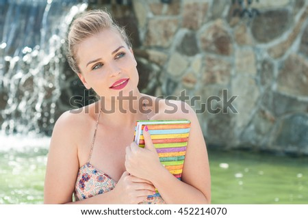 Beautiful woman holding diary or agenda outside on windy sunny weather with waterfall in background and copy space area