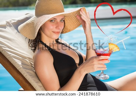 Beautiful woman holding drink by swimming pool against heart - stock photo