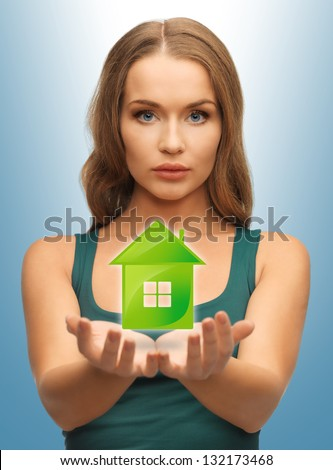 beautiful woman holding green house in her hands - stock photo