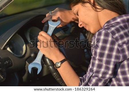 Beautiful woman holding hand wrench in broken car