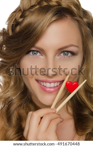 beautiful woman holding heart with chopsticks isolated on white