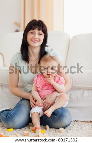 Beautiful woman holding her baby in her arms while sitting on a carpet in the living room
