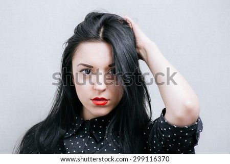 Beautiful woman holding her hand behind her head. On a gray background. - stock photo