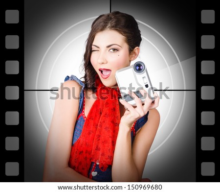 Beautiful woman holding home video camera on vintage film background - stock photo