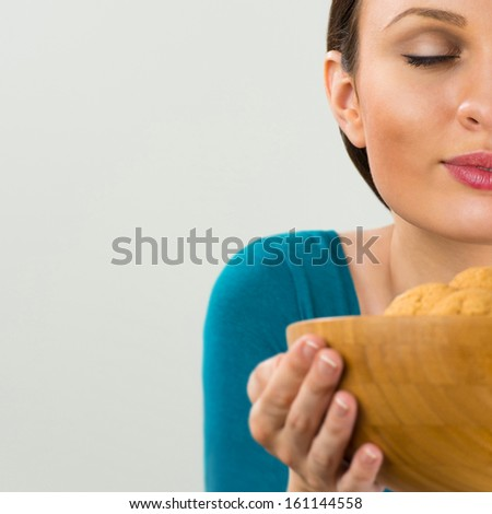 Beautiful woman holding hot fresh smelling oat cookies with closed eyes and relaxing. Enjoying food poster with place for your text on grey background - stock photo