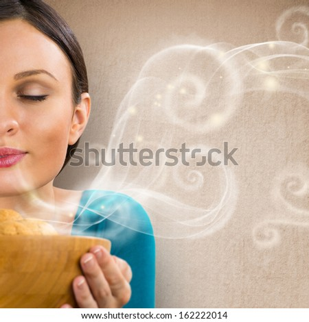 Beautiful woman holding hot fresh smelling oat cookies with closed eyes and relaxing. Retro stylized enjoying food poster with place for your text on grunge background
