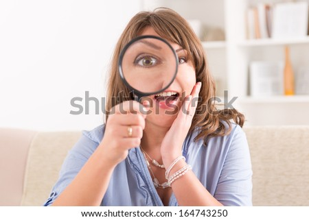 Beautiful woman holding loupe or magnifying glass on her eye - stock photo