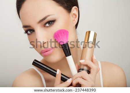 beautiful woman holding makeup set, mascara, liquid powder and brush, studio white